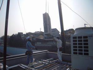 新設の室外機を屋上に搬入しています。